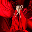 Stock Photo: Two women in red dress with long hair and hearts on red drapery