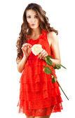 Kobieta w czerwonej sukience z długie kręcone włosy i biała róża w ręku — Zdjęcie stockowe