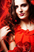 Woman in red dress around red fabric — Stock Photo