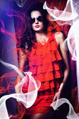 Woman in sunglasses and red dress around fabric — Stock Photo