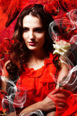 Beautiful hot brunette woman in love in red dress around red fab — Stock Photo