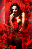 Beautiful hot woman in love in red dress around fabric — Stock Photo