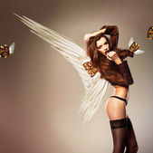 Beautiful erotic woman with wings and flying masks — Stock Photo