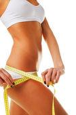 Beautiful sporty woman body with yellow measure — Stock Photo