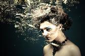 葉の濃い緑色の背景を持つ美しい女性 — ストック写真