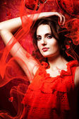 Beautiful woman in love in red dress around fabric — Stock Photo
