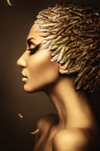 Beautiful woman with gold feather hat — Stock Photo