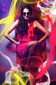 Brunette woman in sunglasses and red dress around fabric — Stock Photo