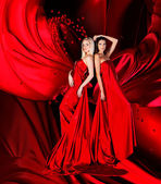 Two women in red dress with long hair and hearts on red drapery — Stock Photo