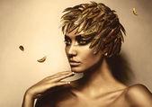 Frau in gold feder hut — Stockfoto