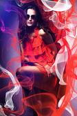 Kobieta w okulary i czerwona sukienka wokół czerwonych i białych tkanin — Zdjęcie stockowe