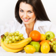 Smiling girl with group of fruits — Stock Photo
