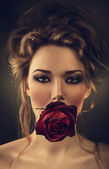 Young beautiful woman and red rose in mouth — Stock Photo