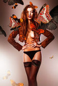 Beautiful erotic sexy woman in jacket and butterflies — Zdjęcie stockowe