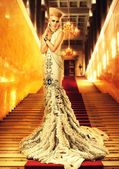 Blond woman in long white dress on red carpet — Stock Photo