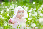 Summer fun, sweet little girl, sitting and blowing dandelion on — Stock Photo