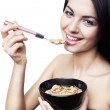 Happy cute woman eating corn flakes — Stock Photo #15259653