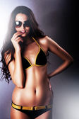 Smiling woman in sunglasses and swimsuit on dark background — Stock Photo