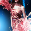 Slim sexy woman in pink dress with long hair and paint splash — Stock Photo