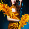 Sensual sexy woman in yellow dress and yellow splash — Stock Photo