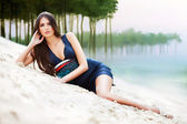 Attractive woman in dress on the forest beach — Stok fotoğraf