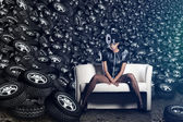 Attractive woman siting in chair on tires — Stock Photo