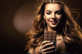 Passionate smiling woman and chocolate block — Stock Photo
