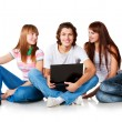 Stock Photo: Three students are siting at ground, smiling and talking