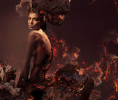 Sexy attractive nude woman in burning ashes — Stock Photo