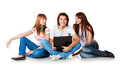 Three students are siting at ground, smiling and talking — Stock Photo