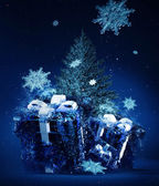 Frozen christmas gifts and blue fir-tree — Stock Photo