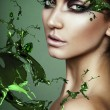 Close up portrait of sexy woman in green plant splash - Stock Photo