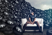 Attractive woman siting in chair on tires on cloudy sky — Stock Photo