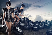 Attractive women running on tires on the cloudy sky — Stock Photo