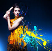 Sensual sexy woman in long yellow dress and splatter — ストック写真