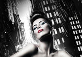 Attractive brunette woman with red lips in rainy city — 图库照片