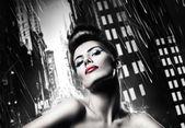 Mulher morena atraente com lábios vermelhos na cidade chuvosa — Foto Stock