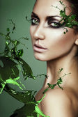Close up portrait of sexy woman in green plant splash — Stock Photo