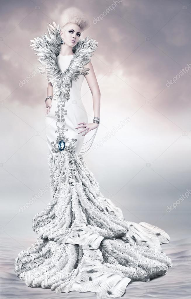 Woman in long white dress with feather collar on sand — Stock Photo #19072441