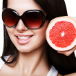 Sexy smiling woman with grapefruit in sundlasses — Stock Photo