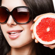 Sexy woman with grapefruit in sundlasses — Stock Photo