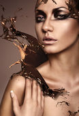 Close up portrait of attractive woman with chocolate splash — Stock Photo