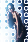 Hot woman in sunglasses with long hair in light room — Stock Photo