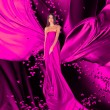 Goddess of love in long red dress with magnificent long hair — Stockfoto
