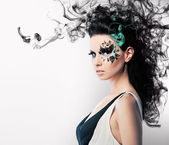 Face art of rhinestones on brunette woman and smoke — Stock Photo
