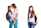 Friends kissing and lonely girl — Foto de Stock