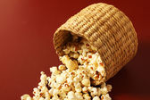 Popcorn in bowl spreading on red background — Stock Photo