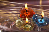 Three candles floating on water bowl — Stok fotoğraf