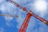 A red crane with blue sky and clouds as background — Stock Photo