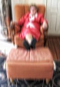 A lens blurred image of an old lady resting in a huge chair — Stock Photo